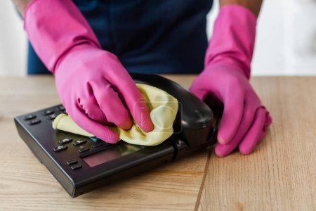 Photo pour Vue recadrée du nettoyant afro-américain dans des gants en caoutchouc téléphone de nettoyage avec chiffon sur la table dans le bureau - image libre de droit