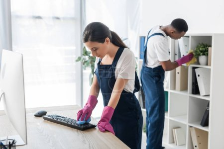 Photo for Selective focus of worker of cleaning service cleaning computer keyboard near African american colleague in office - Royalty Free Image