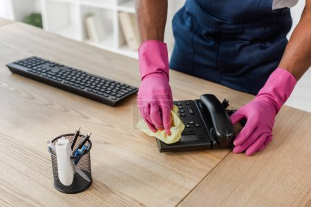 Photo for Cropped view of african american cleaner in workwear and rubber gloves cleaning telephone near stationery and computer keyboard on table - Royalty Free Image