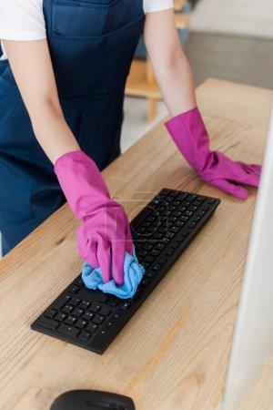 Photo pour Vue recadrée du travailleur du service de nettoyage nettoyage clavier d'ordinateur avec chiffon sur la table - image libre de droit
