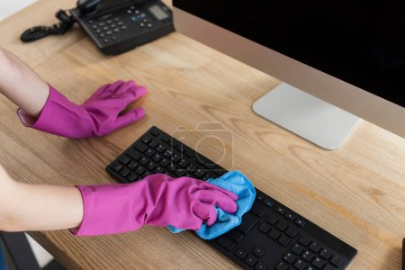Cropped view of cleaner using rag on computer keyboard on table in office