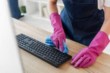 Photo pour Vue recadrée du nettoyant dans les gants en caoutchouc tenant chiffon près du clavier d'ordinateur dans le bureau - image libre de droit