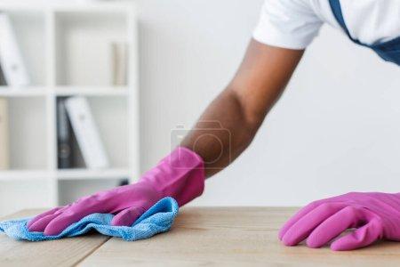 Vista recortada de trabajador afroamericano de servicio de limpieza mesa de oficina de limpieza