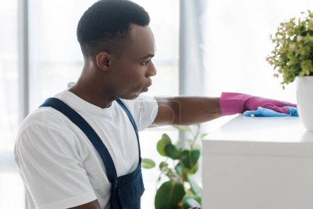 Photo for Selective focus of african american worker of office cleaning service cleaning cupboard with rag - Royalty Free Image