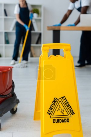 Photo for Selective focus of wet floor sign with attention lettering and multiethnic cleaners working in office - Royalty Free Image