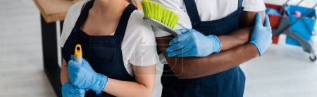 Photo for Panoramic orientation of multiethnic cleaners in uniform holding cleaning supplies in office - Royalty Free Image