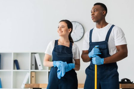 Photo for Smiling cleaner holding rag near african american colleague with mop in office - Royalty Free Image