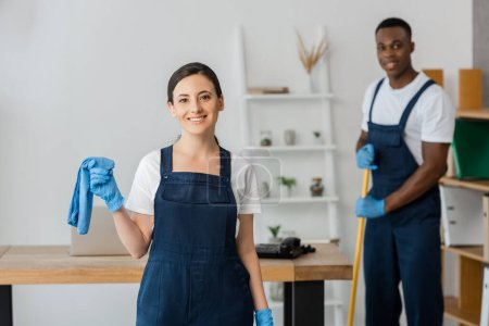 Photo for Selective focus of smiling cleaner in uniform holding rag near african american colleague washing floor in office - Royalty Free Image