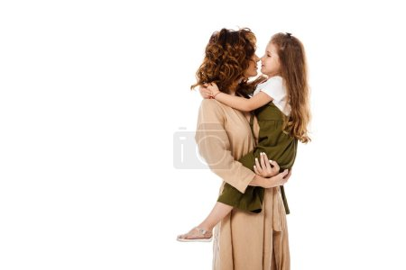 cheerful kid hugging happy and curly mother isolated on white