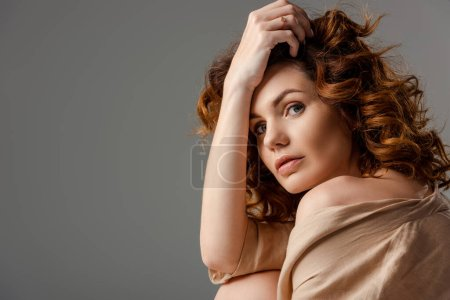 beautiful and curly woman looking at camera isolated on white