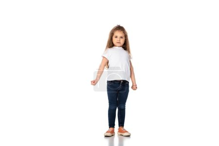 cute kid in white t-shirt and jeans standing on white