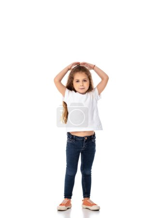 Photo for Cute kid in white t-shirt and jeans looking at camera on white - Royalty Free Image