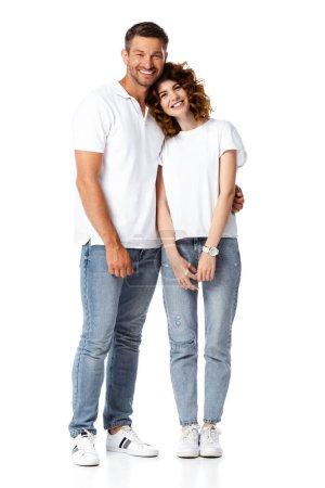 glücklicher Mann lächelt, während er fröhliche Frau auf Weiß umarmt