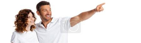 Photo pour Orientation panoramique de l'homme heureux pointant du doigt près femme gaie isolé sur blanc - image libre de droit