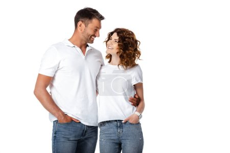 Photo for Happy man and woman standing with hands in pockets while looking at each other isolated on white - Royalty Free Image
