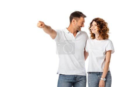 glücklicher Mann, der mit dem Finger zeigt, während er auf eine fröhliche, auf Weiß isolierte Frau blickt