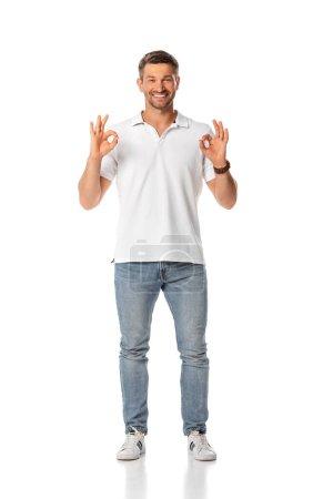 Foto de Alegre hombre mostrando ok signo y de pie sobre blanco - Imagen libre de derechos