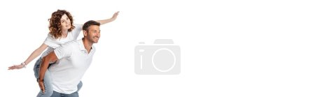 Photo for Website header of cheerful man piggybacking curly wife with outstretched hands isolated on white - Royalty Free Image