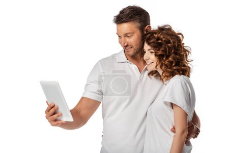 Photo for Positive couple looking at digital tablet isolated on white - Royalty Free Image