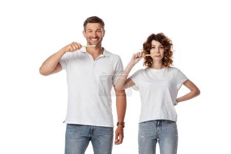 cheerful couple brushing teeth isolated on white