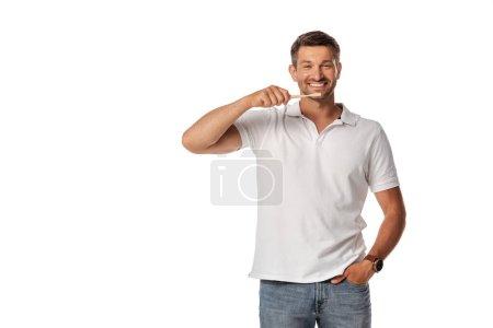 Foto de Hombre alegre sosteniendo el cepillo de dientes y de pie con la mano en el bolsillo aislado en blanco - Imagen libre de derechos