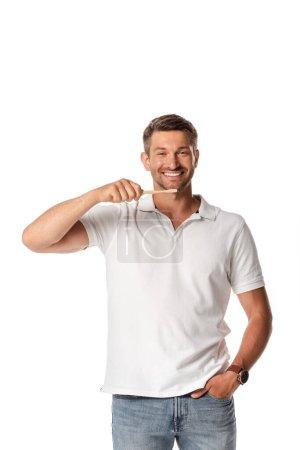 Photo pour Homme heureux tenant brosse à dents et debout avec la main dans la poche isolé sur blanc - image libre de droit