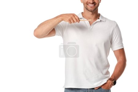 cropped view of cheerful man holding toothbrush and standing with hand in pocket isolated on white