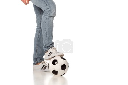 cropped view of man in jeans playing football on white