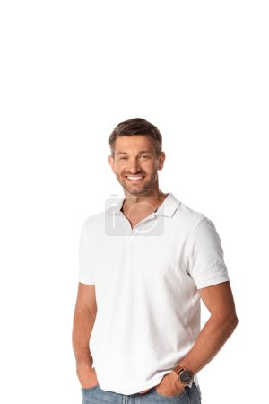 Photo pour Homme gai en t-shirt blanc souriant tout en se tenant avec les mains dans des poches isolées sur blanc - image libre de droit