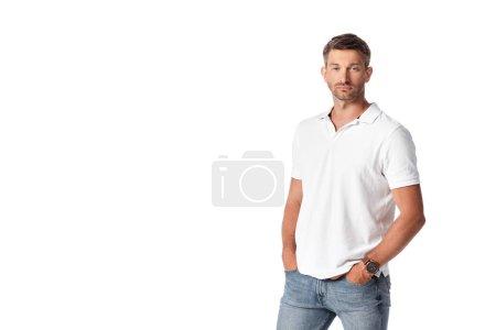 Photo pour Bel homme en t-shirt blanc debout avec les mains dans des poches isolées sur blanc - image libre de droit
