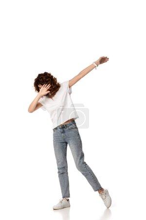 Foto de Mujer rizada haciendo gestos mientras está de pie en blanco - Imagen libre de derechos