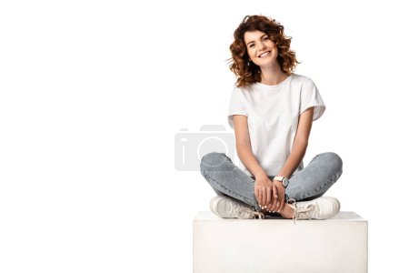 cheerful woman in jeans sitting on cube and smiling isolated on white