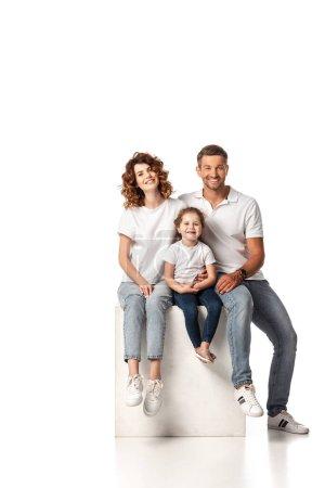 Photo pour Joyeuse famille souriante et assise sur cube sur blanc - image libre de droit