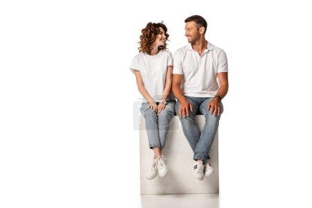 fröhliches Paar lächelt und schaut einander an, während es auf einem weißen Würfel sitzt