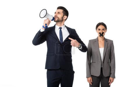 Photo for Bearded businessman pointing with finger while screaming in megaphone near businesswoman with duct tape on mouth isolated on white - Royalty Free Image