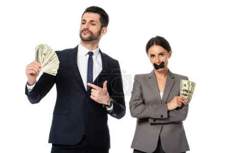 Photo for Businessman holding dollars near businesswoman with duct tape on mouth standing with crossed arms isolated on white - Royalty Free Image