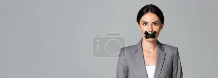 Photo for Panoramic orientation of businesswoman with scotch tape on mouth isolated on grey - Royalty Free Image