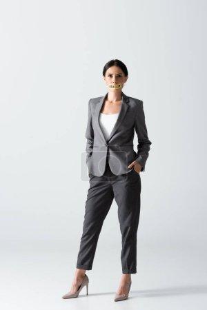 Foto de Mujer de negocios con letras de sexismo en cinta adhesiva mirando a la cámara mientras está de pie con las manos en los bolsillos en blanco - Imagen libre de derechos
