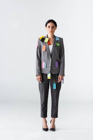 Geschäftsfrau mit Etiketten auf formaler Kleidung, die auf Weiß stehen, Konzept der Ungleichheit zwischen den Geschlechtern
