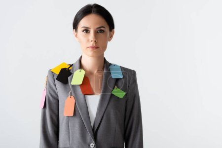 attractive businesswoman with labels on formal wear standing isolated on white, gender inequality concept