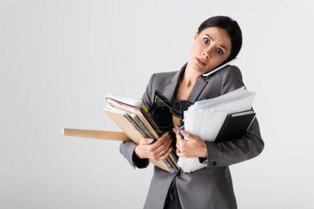 Photo pour Femme d'affaires occupée tenant la calculatrice, tasse en papier, documents, dossiers et cahiers tout en parlant sur smartphone isolé sur blanc - image libre de droit