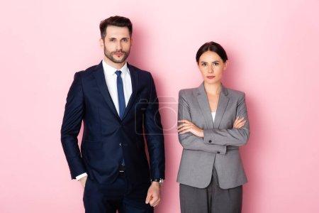 Photo pour Bel homme d'affaires debout avec la main dans la poche près d'une femme d'affaires avec les bras croisés sur rose, concept d'égalité des sexes - image libre de droit