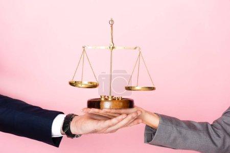 Photo pour Vue recadrée de l'homme d'affaires et de la femme d'affaires tenant des échelles d'or isolées sur rose, concept d'égalité des sexes - image libre de droit