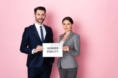 handsome businessman and businesswoman holding placard with gender equality lettering on pink