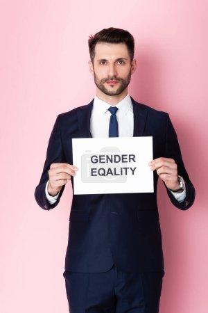 Photo pour Homme d'affaires tenant une pancarte avec des lettres d'égalité des sexes sur rose - image libre de droit