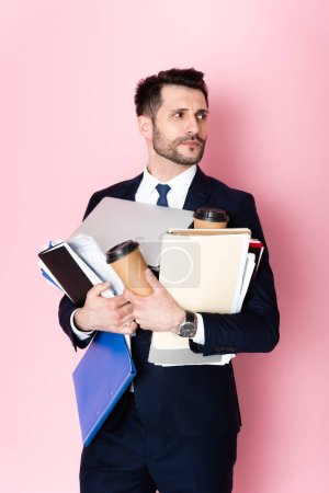 Photo for Handsome businessman holding paper cups, laptop, folders and notebooks while looking away on pink - Royalty Free Image