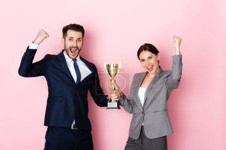 Photo for Excited businessman and businesswoman holding trophy and gesturing on pink, gender equality concept - Royalty Free Image