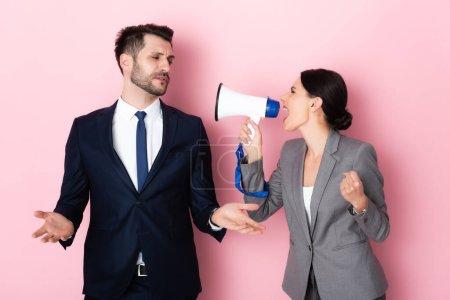 Photo pour Femme émotionnelle crier en mégaphone près de l'homme d'affaires geste sur rose - image libre de droit