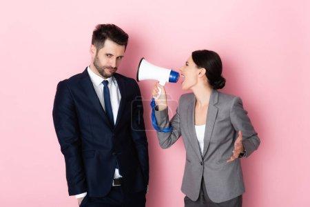 Photo pour Femme émotionnelle crier dans mégaphone près offensé homme d'affaires sur rose - image libre de droit