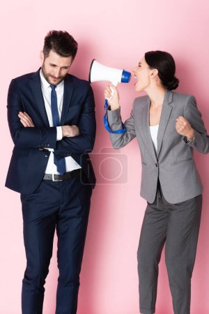 emotional woman screaming in megaphone near businessman standing with crossed arms on pink